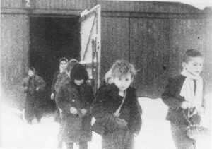 Soon after liberation, surviving children of the Auschwitz camp walk out of the children's barracks. Poland, after January 27, 1945.
